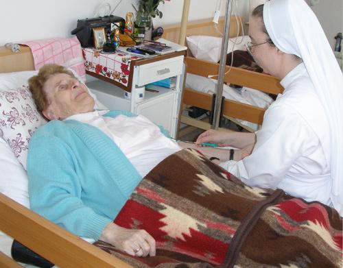 zdjęcie, siostra trzyma pacjentkę za rękę